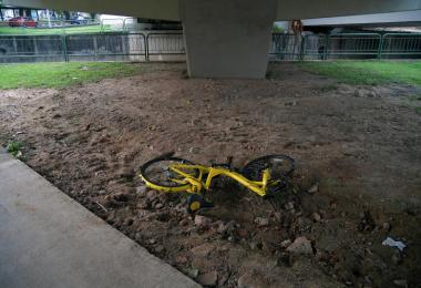 一辆黄色ofo脚踏车被丢置在高架桥下。