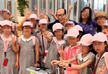 李嘉诚开心地和孩子们合照。(微博)