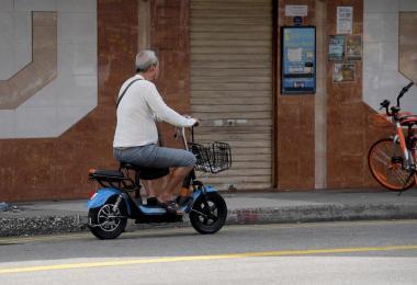 在芽笼一带,有位大叔将电动踏板车开上马路。PMD不能驶上马路,但偏偏还是有人以身试法.(海峡时报)