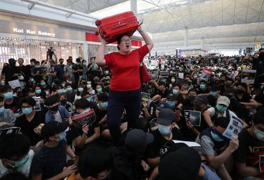 大妈扛行李逃难,在香港机场杀出一条血路的照片在网络上爆红。本地媒体报道说,大妈原来是新加坡人。