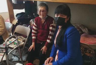 脸部依然淤青未消肿的谢萧珍奶奶(左)与看望她的当地华侨。(互联网)