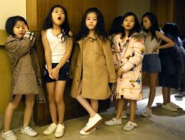 进入化妆区前,童模们耐心地排队等候。(互联网)