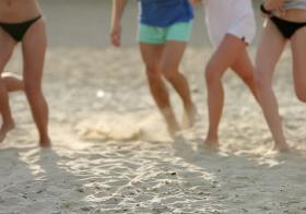 young people playing on the beach
