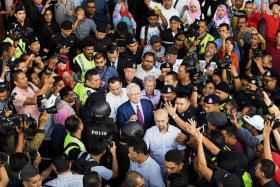 马来西亚前首相纳吉(中间戴眼镜)今天下午交保之后离开高庭时,被支持者和记者们里三层、外三层包围。