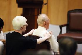 建国总理李光耀夫人柯玉芝于2010年10月2日在家中逝世。李显龙总理的长子李毅鹏(后)在葬礼上把双手轻放在祖父李资政的肩上,给予宽慰。(联合早报)