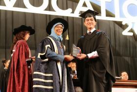 第一届奖学金得主从第一个女总统手上接过奖状。