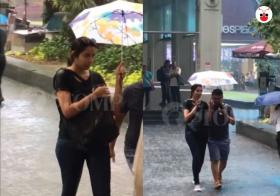 Young lady shelters strangers to and fro Raffles Place MRT Station during heavy downpour