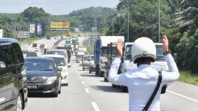 """马国许多民众都希望回乡过开斋节,交警在各主要大道设路检,确保没有人""""偷渡""""回乡。"""