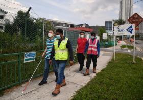 外籍客工扶视障人士过马路