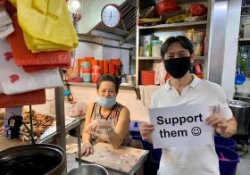 """义顺集选区议员黄国光2020年6月拿着一张写着""""支持他们""""(Support Them)和画有笑脸的纸张,到小贩中心呼吁公众支持小贩"""